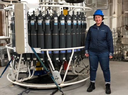 CAPSTAN student Jess wears her hardhat as she stands next to the CTD rosette.  The rosette is taller than Jess, with the top of the niskin bottles lining its edge about even with her head.  The sensors (CTD itself) are at the lower part of the cage.