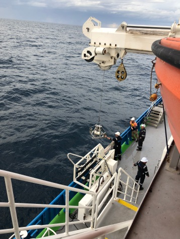A view of the sediment grab sampler being deployed off the starboard winch from a few levels above.  The upper deck is a safe spot for CAPSTAN students to stand without being in the way when they want to see the deployment.